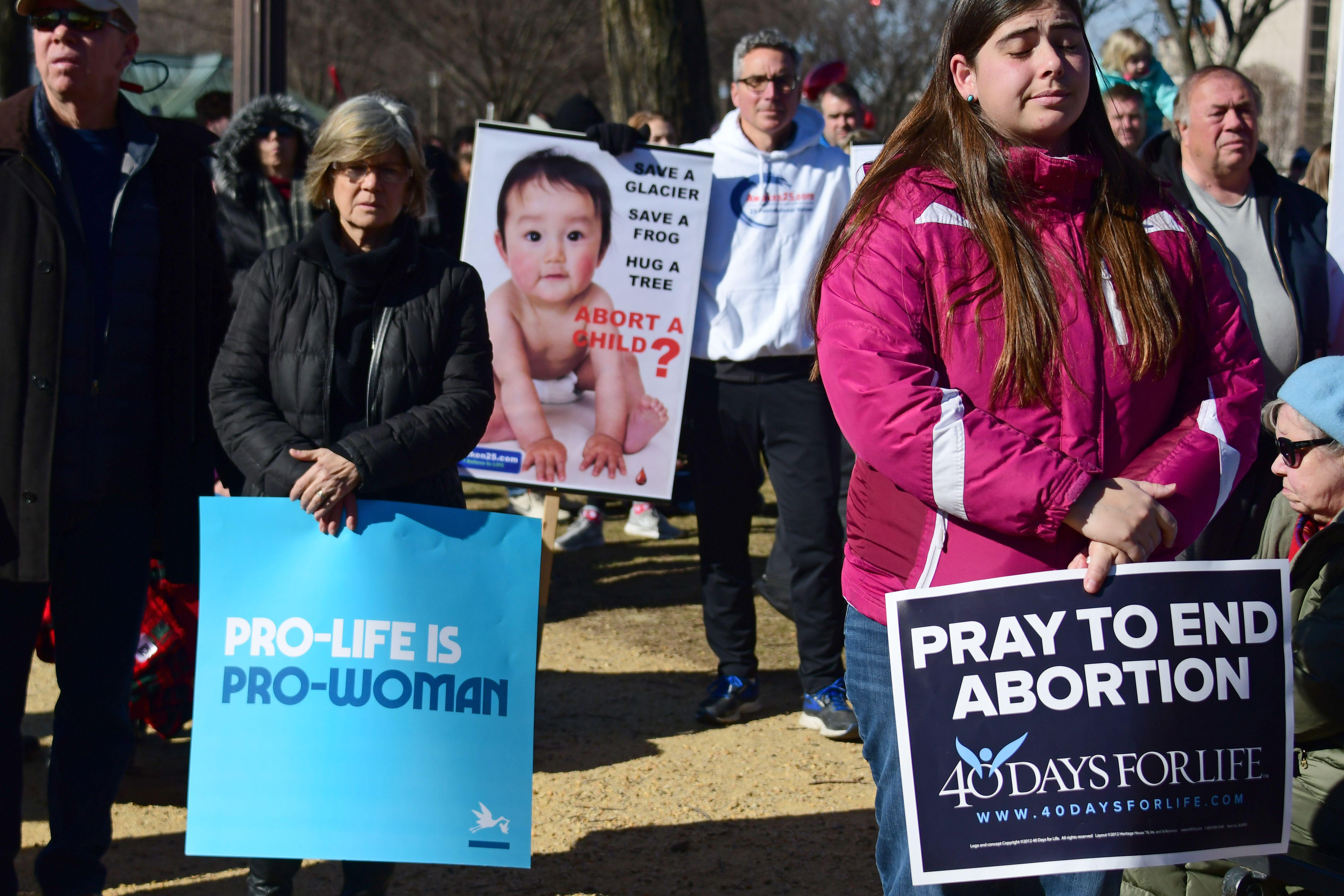 Protesters holding anti-abortion signs listen to a prayer on the National Mall.